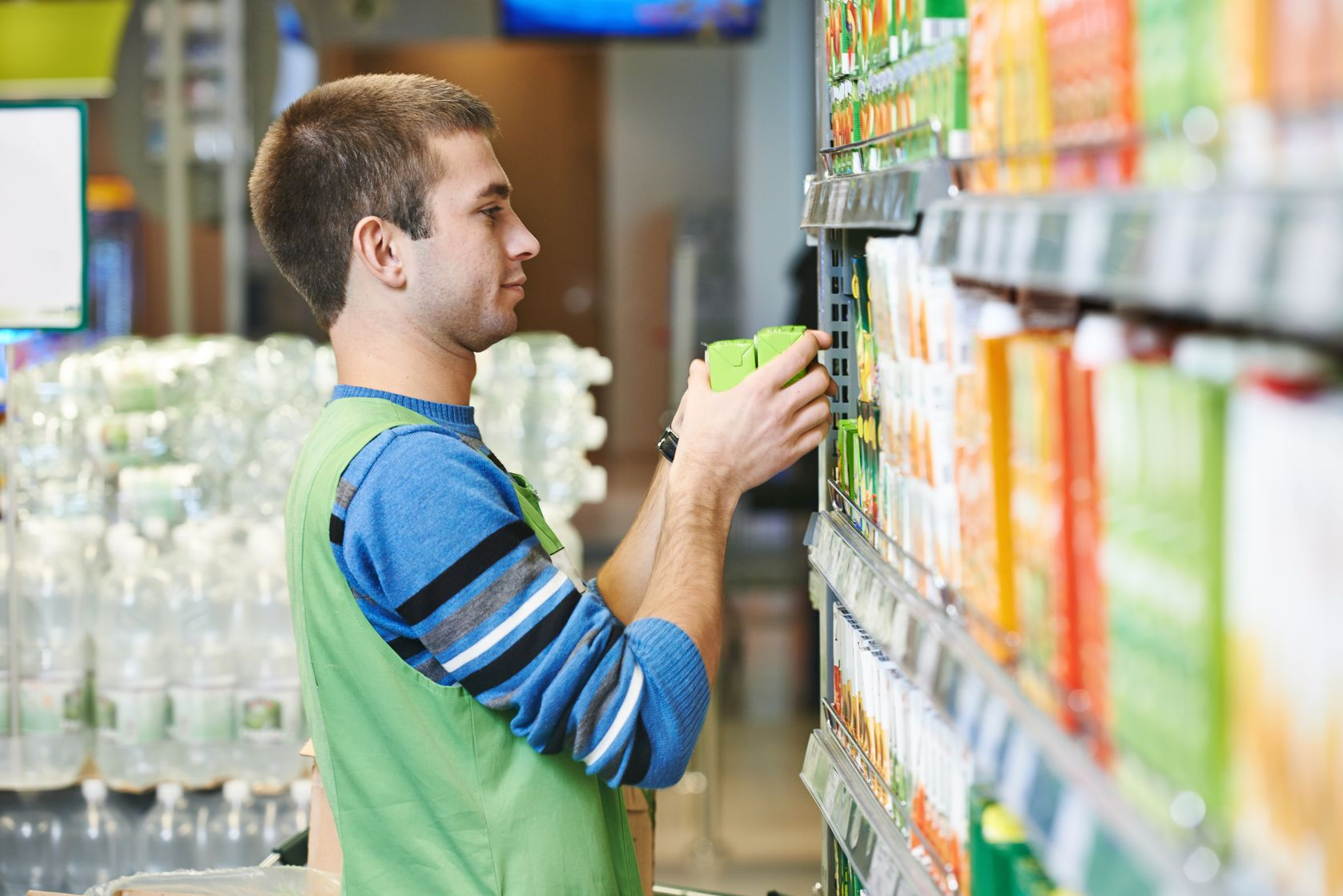 young man putting products on shelves